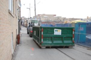 Dumpster blocking alley.