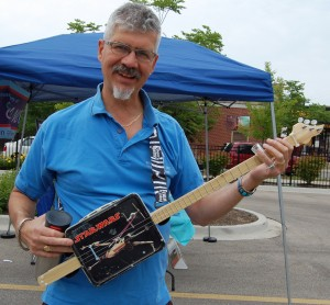 Richard Trumbo, owner of Music House, and his homemade lunchbox guitar